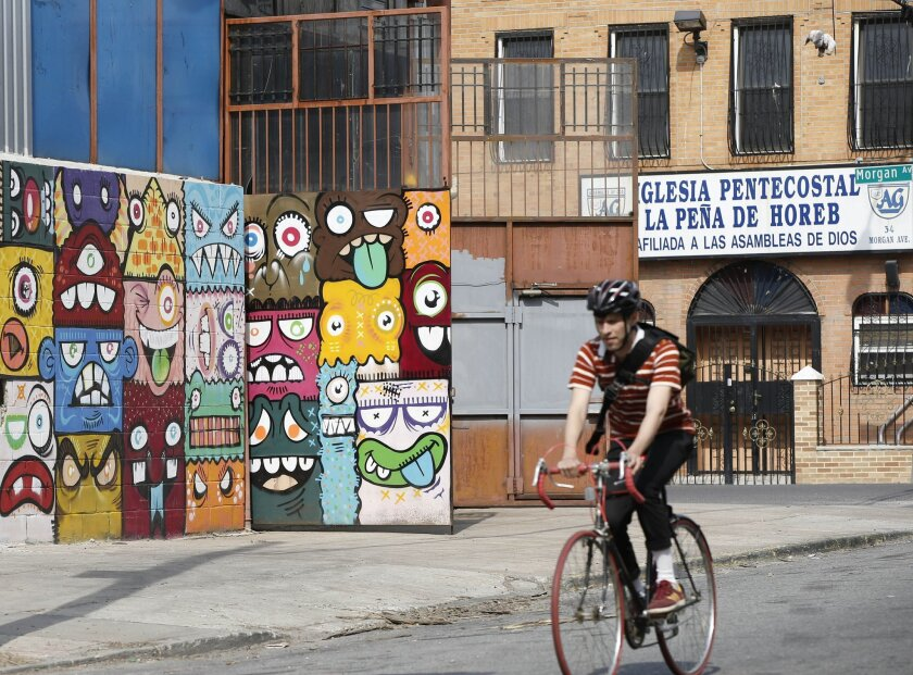 A cyclist pedals by a a street art mural and a storefront church, Tuesday, April 22, 2014, in Brooklyn's Bushwick neighborhood in New York. The neighborhood, once considered dangerous, is beginning to attract tourists and hipsters. (AP Photo/Kathy Willens)