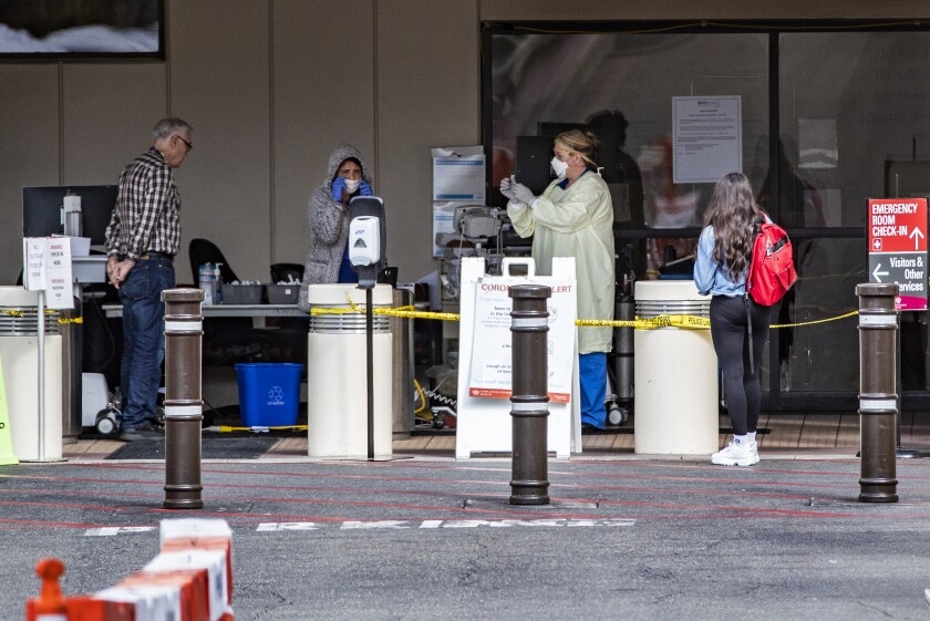 Medical personnel screen patients outside the emergency room at Loma Linda University Health last week.