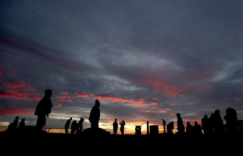 A small crowd takes in the sunset from the top of Signal Hill.