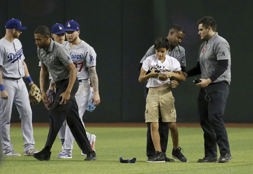 Chase Field security detained a spectator who ran onto the field before he reached Dodgers' outfielders, from left, Kyle Garlick, Enrique Hernandez and Alex Verdugo.
