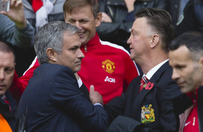 FILE- In this Sunday Oct. 26, 2014, file photo, the then Chelsea's manager Jose Mourinho, left, greets Manchester United manager Louis van Gaal, before the English Premier League soccer match between Manchester United and Chelsea at Old Trafford Stadium, Manchester, England. Manchester United hired