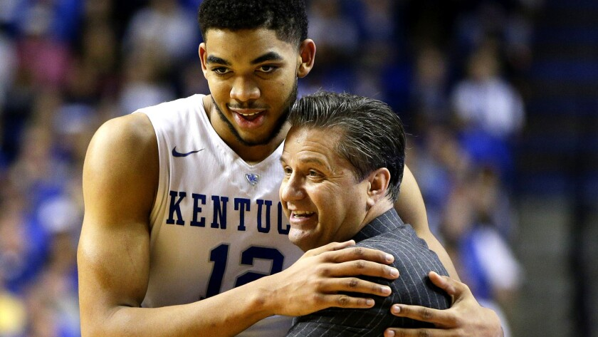 Center Karl-Anthony Towns (12), the No. 1 pick in last spring's NBA draft, gets a big hug from Kentucky Coach John Calipari during a timeout in an SEC win over Georgia.
