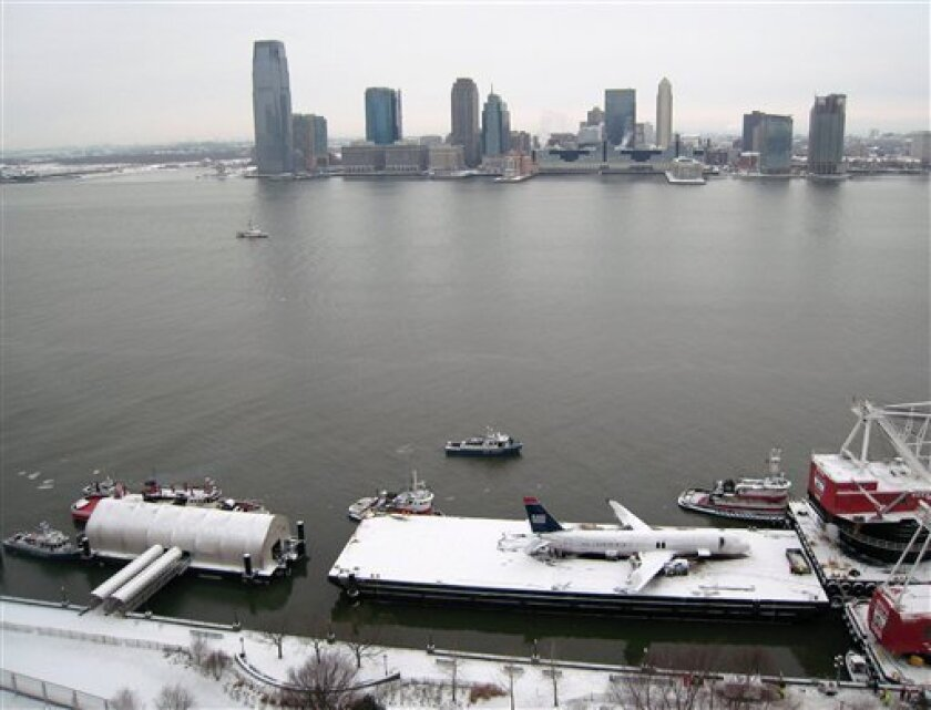 With Jersey City in the background, a crippled US Airways Flight 1549 rests on a barge on the Hudson River in New York, Sunday, Jan. 18, 2009, after being lifted from the water late Saturday night. The aircraft will be moved to an undisclosed location for inspection by National Transportation Safet