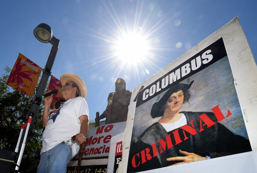 Olin Tezcatlipoca from the Mexica Movement speaks to demonstrators in front of a statue of Christopher Columbus in Los Angeles' Grand Park on Sunday.