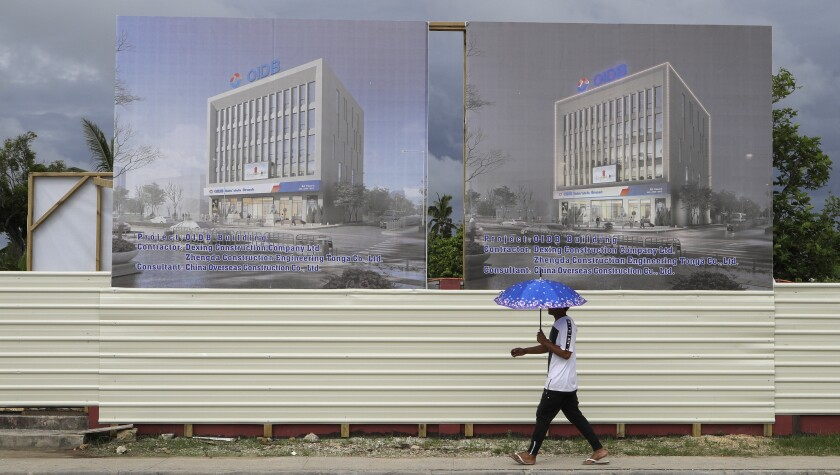 FILE - In this April 10, 2019, file photo, a man walks past a development site for a Chinese Investment bank in Nuku'alofa, Tonga. The Sydney-based think tank Lowy Institute released its annual Pacific Aid Map, Wednesday, Sept. 29, 2021, saying China gave significantly less aid to the Pacific in recent years despite Beijing's diplomatic efforts to increase its influence in the region. (AP Photo/Mark Baker, File)