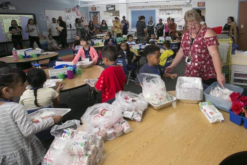 Kindergarten teacher Jennifer Smart, right, helps here students get settled in class and helps them get some breakfast on the first day of class at Zamorano Elementary School in the Bay Terrace community of San Diego.