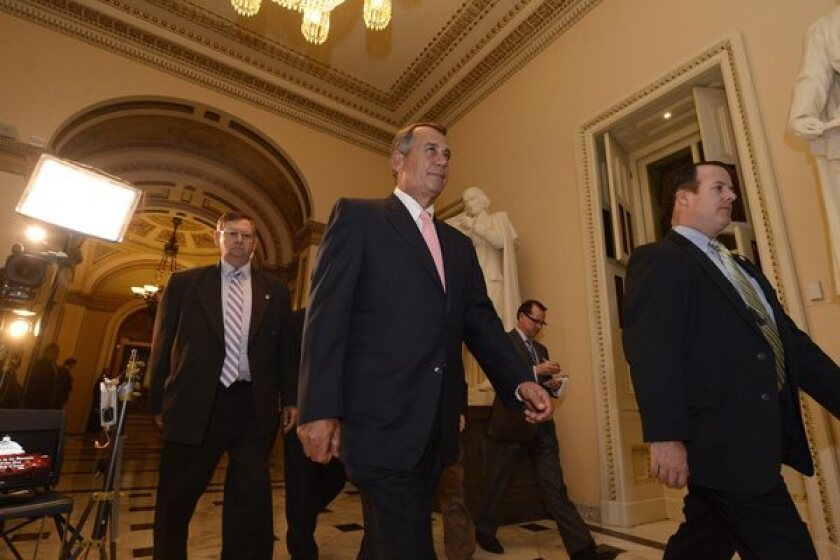 Speaker of the House John Boehner, center, is seen leaving the House Chamber. The Senate has so far rejected a House version of the resolution that included language limiting the Affordable Care Act.