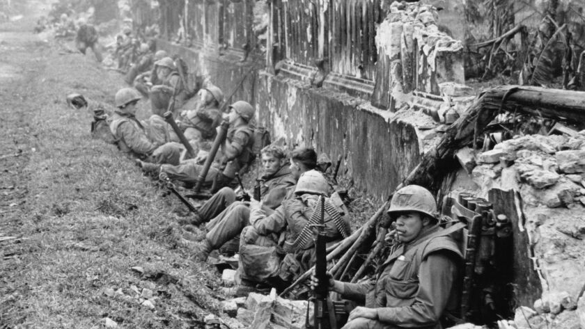 U.S. Marines rest alongside a battered wall of Hue's imperial palace after a battle for the Citadel