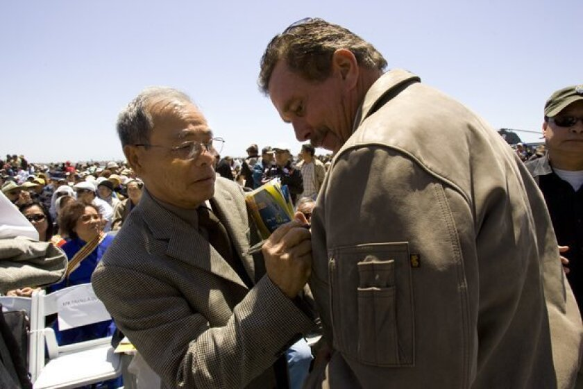 Bung Ly takes signs autographs for people on board the USS Midway.  Ly was the daring pilot who landed his single seat cessna with his wife and five children on the USS MIdway.