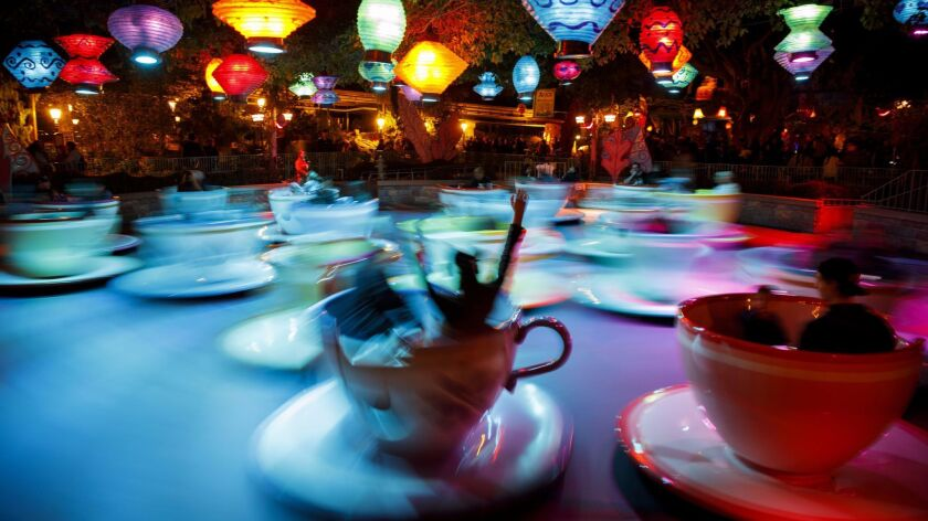 "Attendees spin inside oversized teacups on the ""Mad Tea Party"" ride at Disneyland Park on Sunday, Ja"