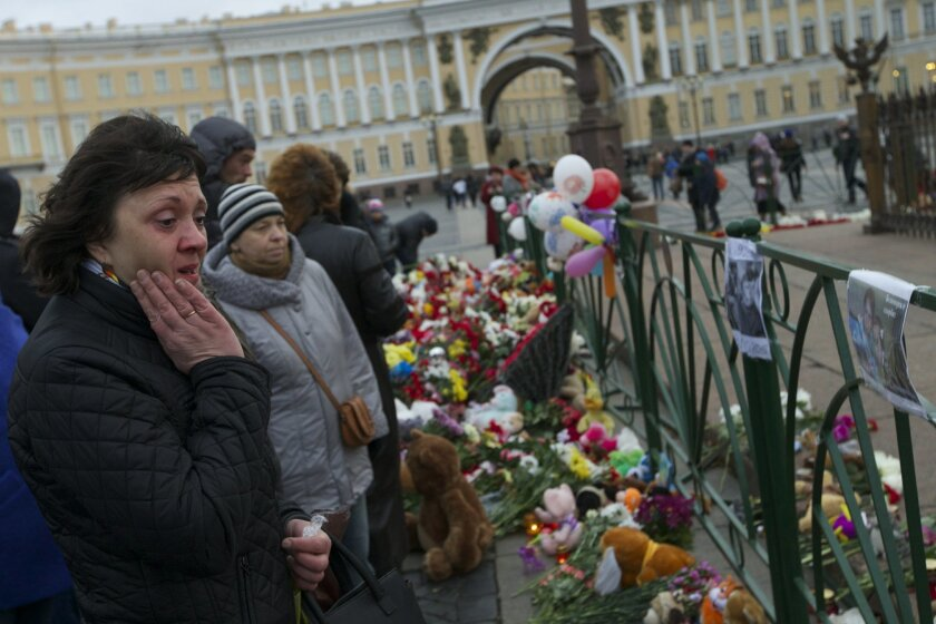 People look at photos of the plane crash victims attahced to the fence at Dvortsovaya (Palace) Square in St. Petersburg, Russia, on Monday, Nov. 2, 2015. In a massive outpouring of grief, thousands of people flocked to St. Petersburg's airport, laying flowers, soft toys and paper planes next to the