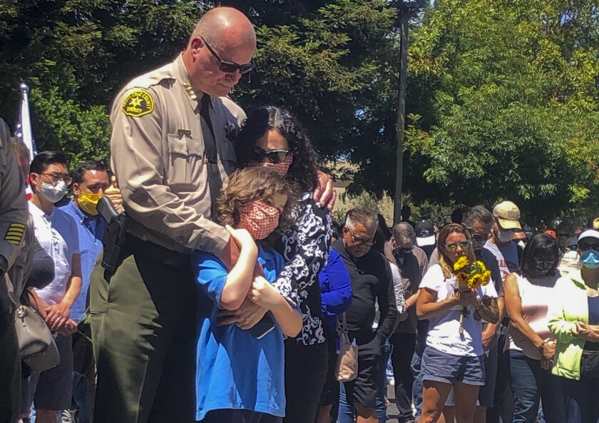 Santa Cruz County Sheriff Jim Hart stands with his wife and child as people pay their respects to Sgt. Damon Gutzwiller.