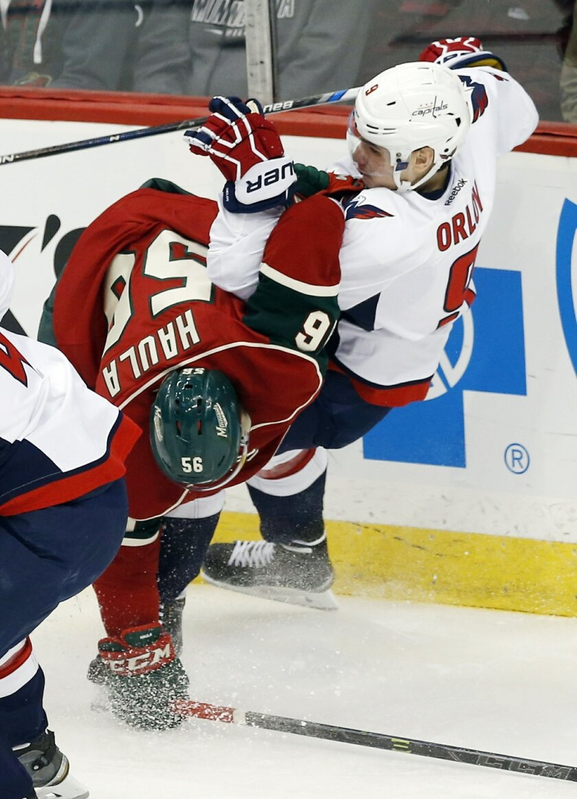 Washington Capitals' Dmitry Orlov, right, of Russia, falls as he is hit by Minnesota Willd's Erik Haula of Finland in the first period of an NHL hockey game, Thursday, Feb. 11, 2016, in St. Paul, Minn. (AP Photo/Jim Mone)
