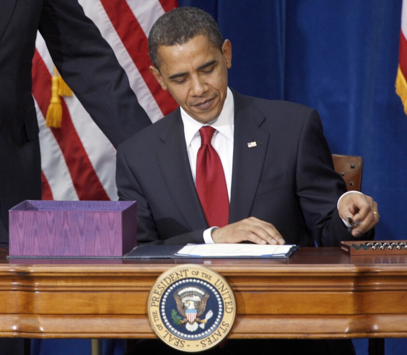 President Obama, in a file photo, picks up a pen to sign the economic stimulus bill.