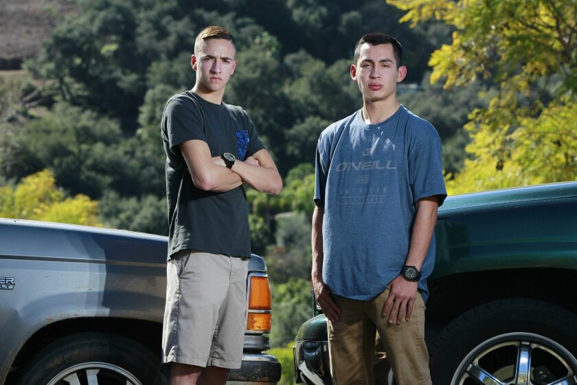 Brandon Cappelletti (left), 18, and Sam Serrato, (right), 16, stand next to their cars on Tuesday in Escondido, California. Both are facing a misdemeanor and expulsion from San Pasqual High School under a zero tolerance policy that says students can't bring a knife to campus under any circumstances