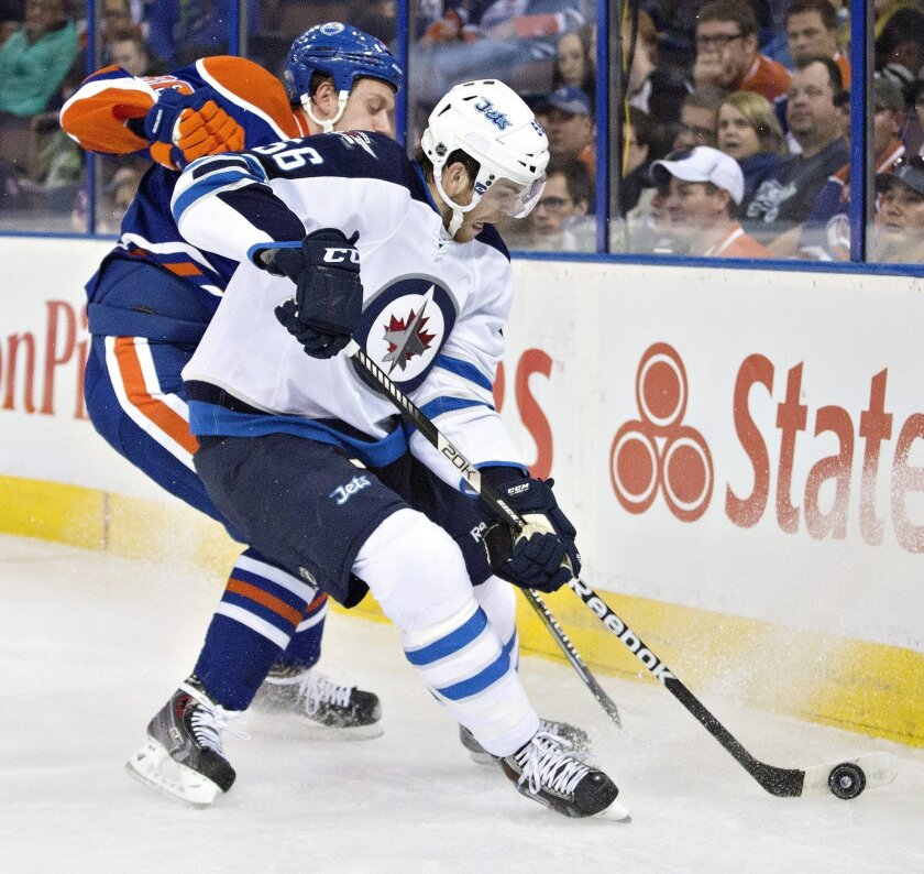 Winnipeg Jets Adam Lowry (56) and Edmonton Oilers Nikita Nikitin (86) battle for the puck during first period NHL hockey action in Edmonton, Alberta, on Monday Sept. 29, 2014. (AP Photo/The Canadian Press, Jason Franson)