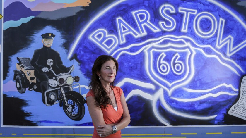 Jane Laraman-Brockhurst, former president of Main Street Murals and current director of Desert Discovery Center, stands near a mural adjacent to Route 66. The murals commemorate California and Barstow history.