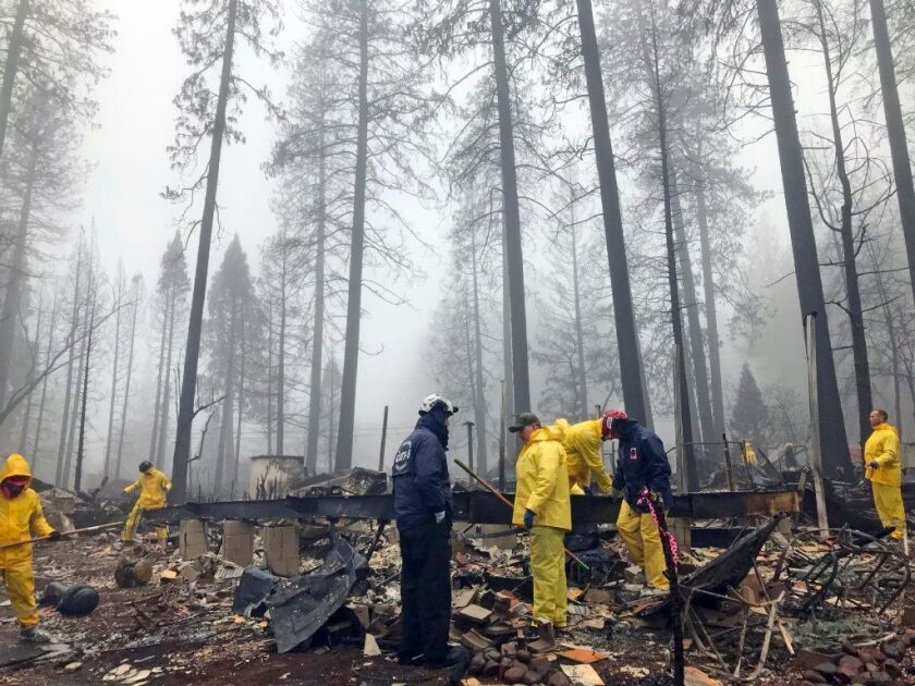 In this Nov. 23, 2018, file photo, volunteers resume their search for human remains at a mobile home park in Paradise, Calif., following a brief delay to let a downpour pass. The death toll from the massive Camp Fire jumped to 88 on Monday.