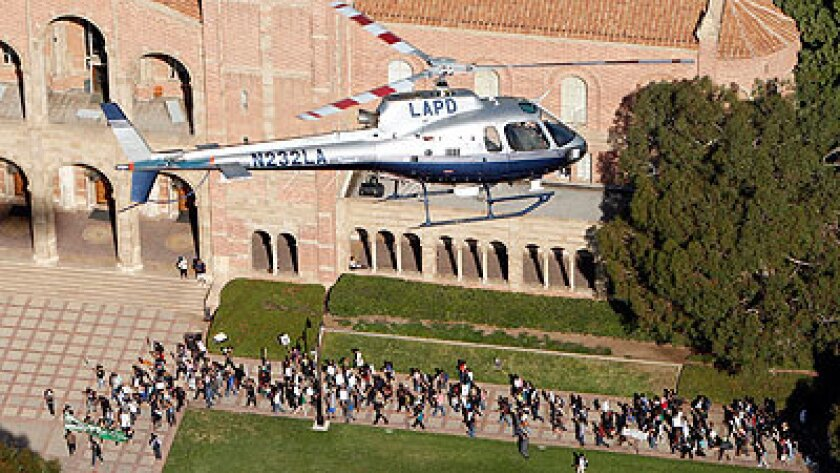 A Los Angeles Police Department helicopter keeps watch on protesters marching through the UCLA campus in Westwood.