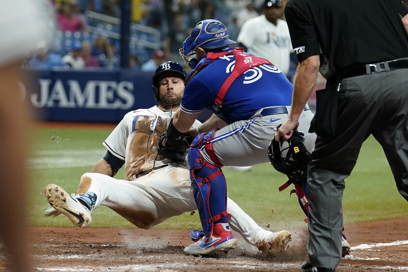 El mexicano Alejandro Kirk, de los Azulejos de Toronto, pone out a Kevin Kiermaier, de los Rays de Tampa Bay, en el juego del lunes 20 de septiembre de 2021 (AP Foto/Chris O'Meara)