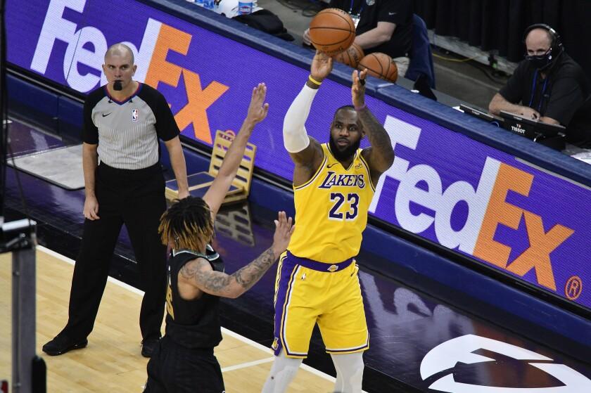 El alero de los Lakers de Los Ángeles LeBron James lanza el balón sobre el alero de los Grizzlies