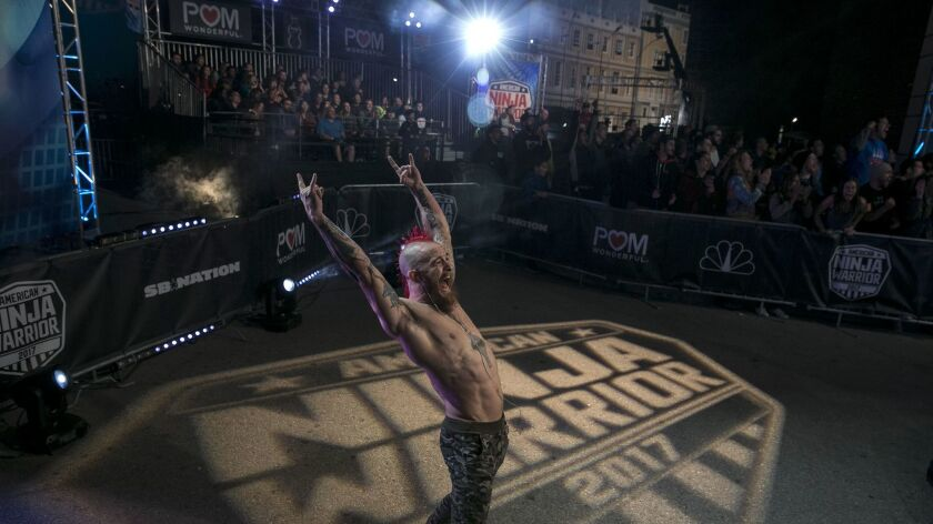 """Stephen Seiver cheers on a fellow athlete competing in the NBC production of """"American Ninja Warrior"""