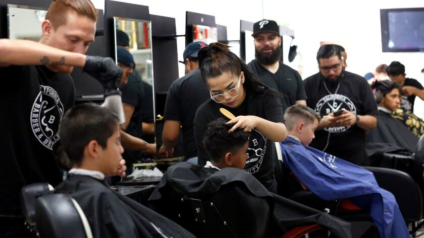 Barbers in training give free hair cuts to young students during the second annual Back-to-School Haircut Drive sponsored by the Larry Himmel Neighborhood Foundation.