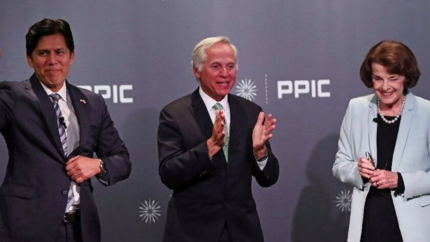 Mark Baldassare, center, of the Public Policy Institute of California, applauds at the end of the debate he moderated between state Sen. Kevin de León (D-Los Angeles) and U.S. Sen. Dianne Feinstein on Wednesday in San Francisco.