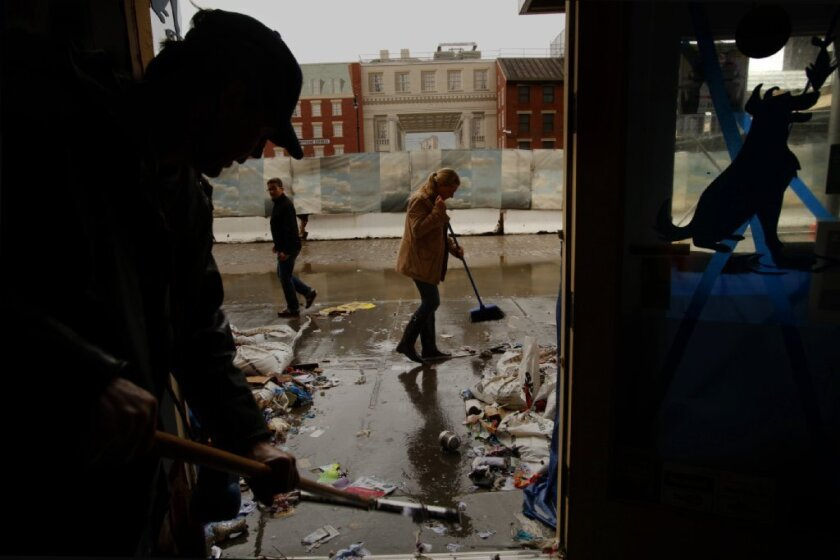 People clean up a store in lower Manhattan after Superstorm Sandy in 2012.