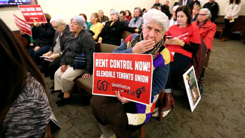 A woman holds a Glendale Tenants Union sign during the council meeting at Glendale City Hall on Tues