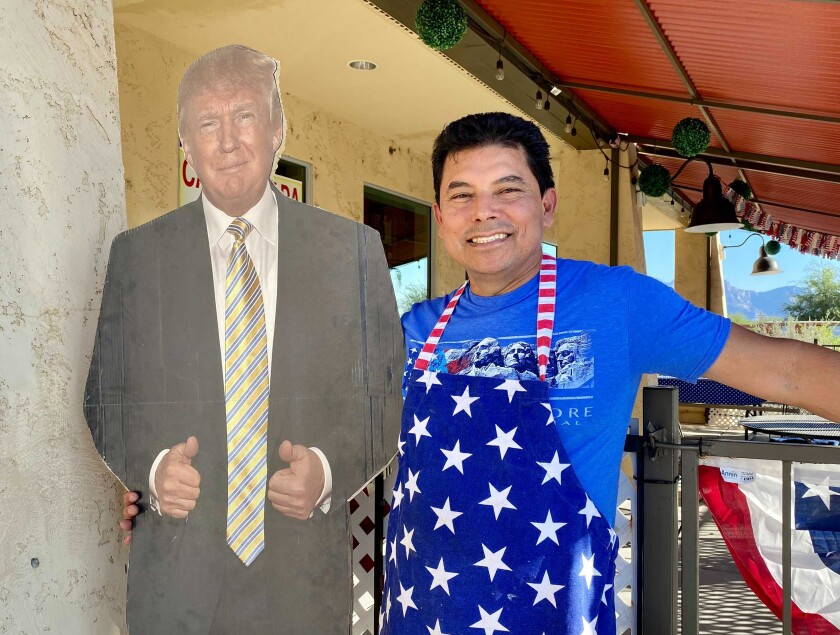 Jorge Rivas wears a red white and blue apron and smiles next to a cardboard cutout of President Trump