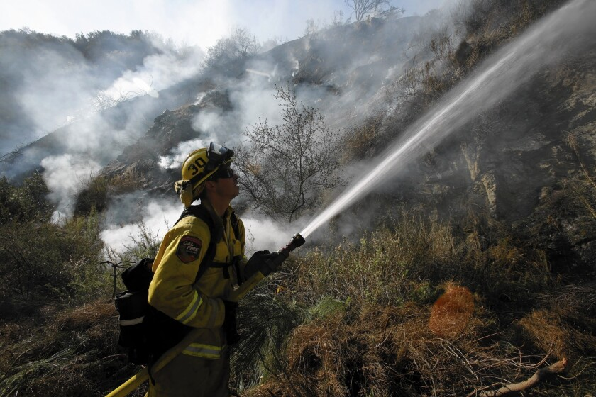 CalFire firefighter Jeff Newby sprays water on smoldering brush burned by the Colby fire along Highway 39 in Azusa on Friday. Gov. Jerry Brown's drought emergency declaration calls on state agencies to hire additional seasonal firefighters this year to respond to elevated wildfire risk.
