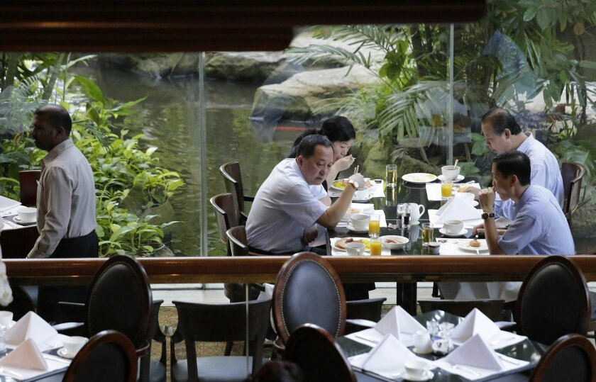 North Korea's nuclear negotiators including senior nuclear negotiator Ri Yong Ho, fromt center, meet for breakfast, Sunday, Jan. 18, 2015 in Singapore. North Korea's chief nuclear envoy and former U.S. negotiators and security experts were in Singapore to discuss nuclear issues at meetings which st