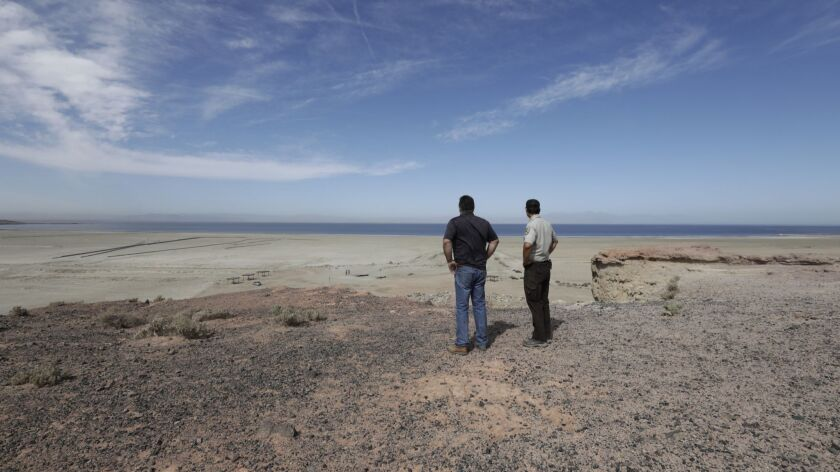 An air pollution control officer and a naturalist examine the state-funded habitat restoration and dust suppression project at Red Hill Bay overlooking the Salton Sea in Calif. on April 11, 2018.