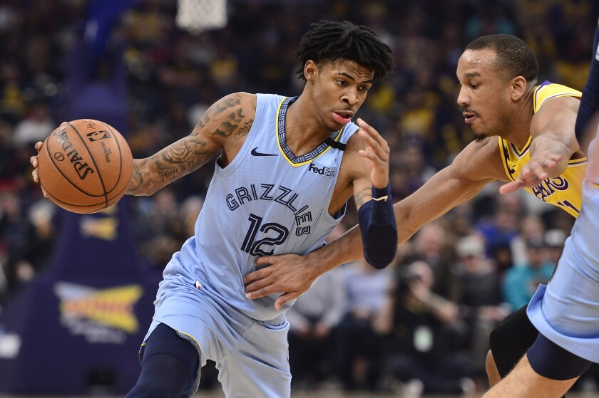 Grizzlies guard Ja Morant tries to shake Lakers guard Avery Bradley on a drive during the first half of a game Feb. 29, 2020, in Memphis, Tenn.