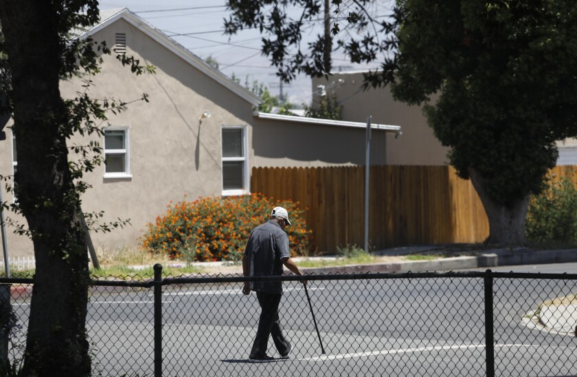 A man with a cane walks through a North Hollywood neighborhood.