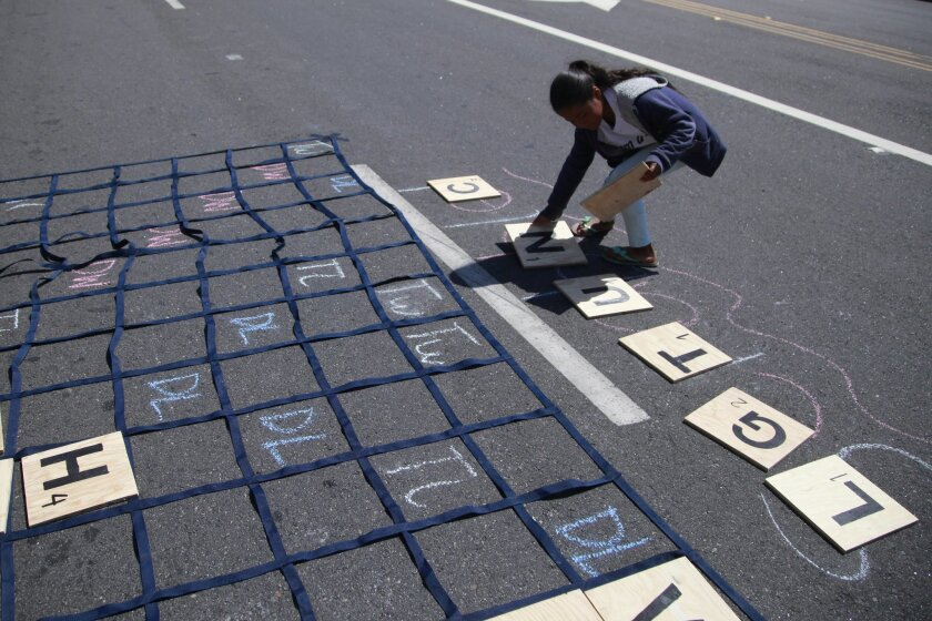 Kaylee Jenis, 7, sorts out letters while playing an oversized game of Scrabble set-up in the middle of the street on Grand Avenue in Escondido. The Cicliovia event cordoned several blocks along Grand and encouraged the community to come out and ride their bikes and play games in the street but the