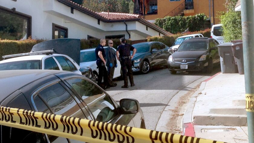Police investigate the scene where three men were found dead after neighbors reported gunshots early