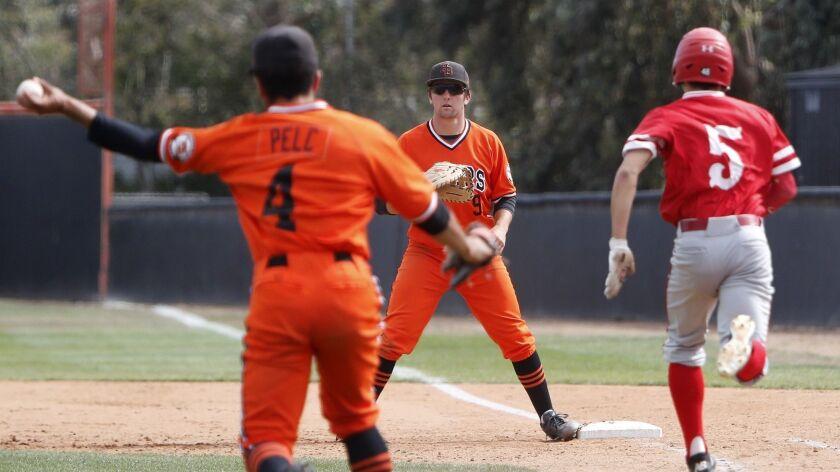 Huntington Beach High's Josh Hahn (9) waits as starting pitcher Eddie Pelc (4) throws Los Alamitos'