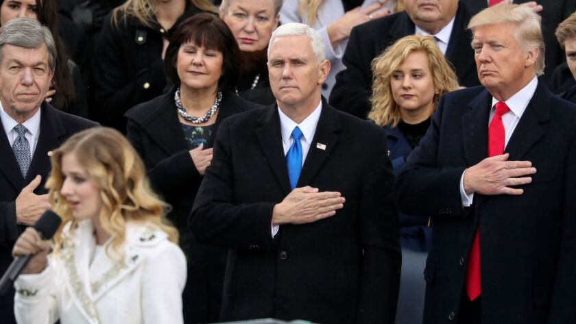 Vice President Mike Pence and President Trump listen to Jackie Evancho sing the national anthem during Trump's inauguration.