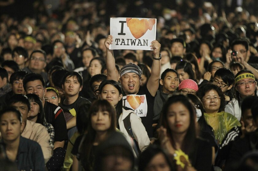 """File- In this March 30, 2014 file photo, a protester displays a banner supporting Taiwan during a massive protest against China in front of the Presidential Building in Taipei, Taiwan. Taiwan struggles with its identity as it retains its official name """"Republic of China,"""" along with a constitution"""
