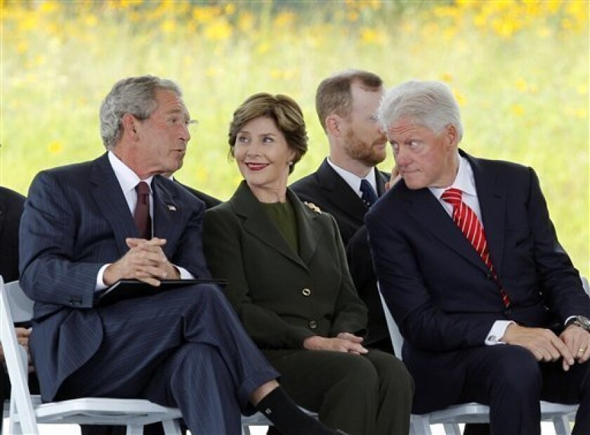 Former President George W. Bush speaks to former President Bill Clinton as former first lady Laura Bush looks on after taking the stage at the dedication of phase 1 of the permanent Flight 93 National Memorial near the crash site of Flight 93 in Shanksville, Pa. Saturday Sept. 10, 2011. (AP Photo/Amy Sancetta)