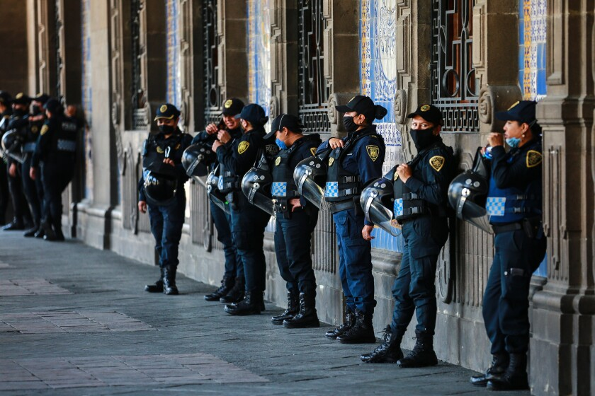Police officers stand guard outside a Mexico City municipal building on Thursday. While most countries and major cities have ordered a lockdown to halt COVID-19 spread, Mexico's president has not called for strict measures.