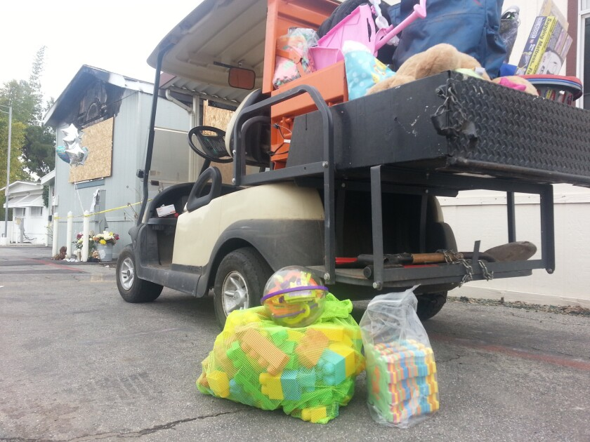 Toys and other donations for the Flores family filled a golf cart at Green Crest Mobile Home Park in Escondido on Tuesday. In the background, the front window of the family's home remains boarded up after a fire on Dec. 29 resulted in the deaths of two children.