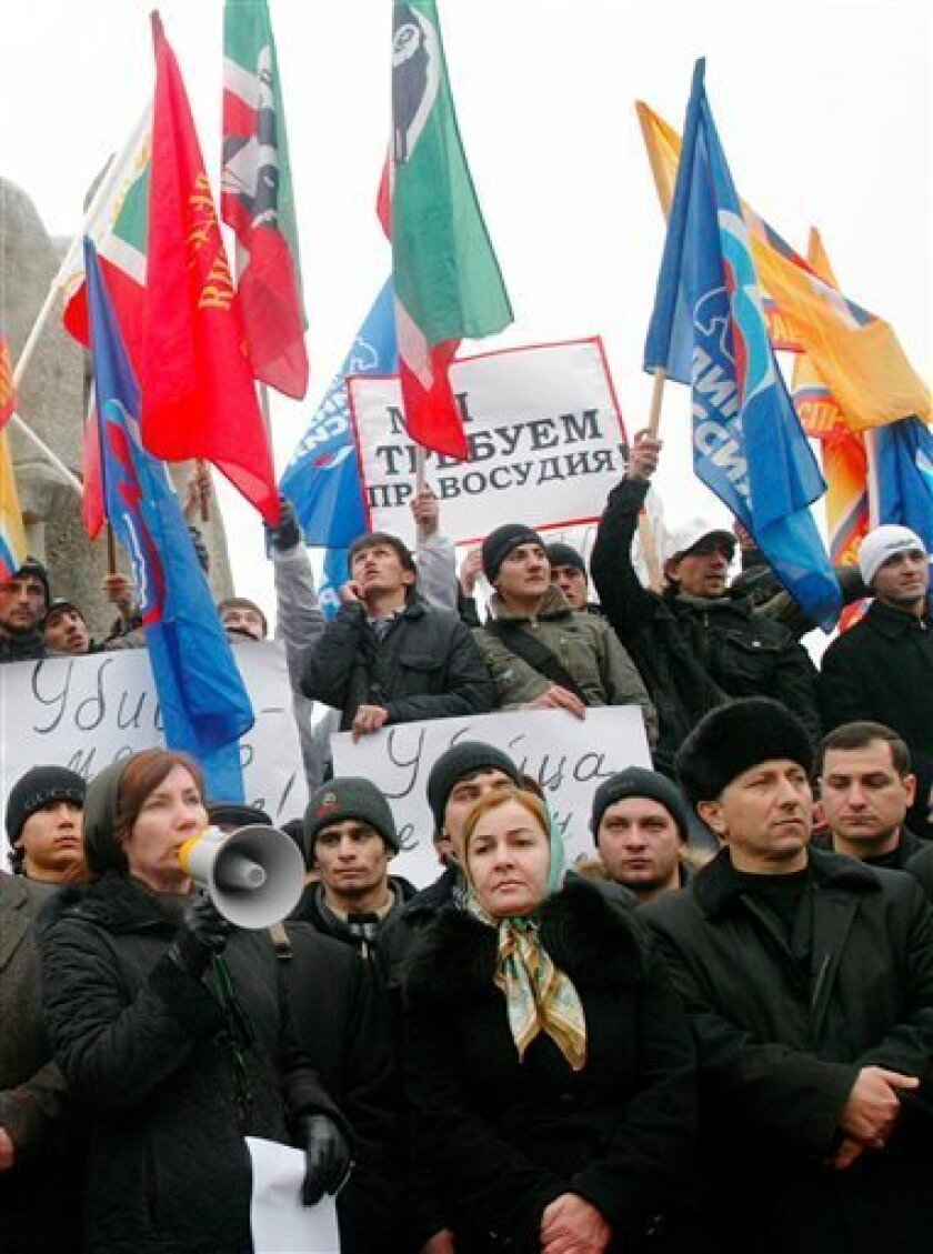 """People protest against the recent assassination of human-rights lawyer Stanislav Markelov in Chechnya's capital Grozny on Tuesday, Jan. 20, 2009, the day after the attack. The poster at center reads: """"We demand justice!"""" Markelov, who had opposed the early release of a Russian colonel convicted of"""