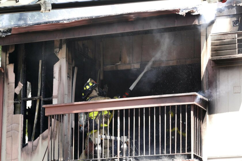 Firefighters extinguish fire on the outside of an Adobe Falls Road condominium that was started by a cigarette causing $350,000 damage.
