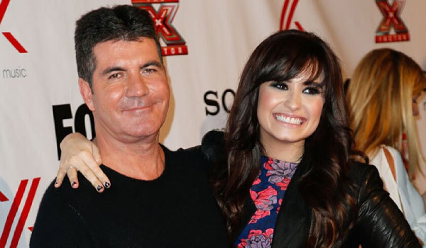 """""""X Factor"""" judges Simon Cowell and Demi Lovato at a party in 2012."""