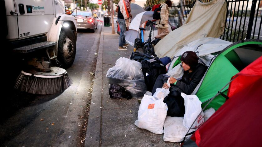 A homeless man packs his belongings outside his tent on the sidewalk in the 6600 block of Selma Avenue in Hollywood on April 8.