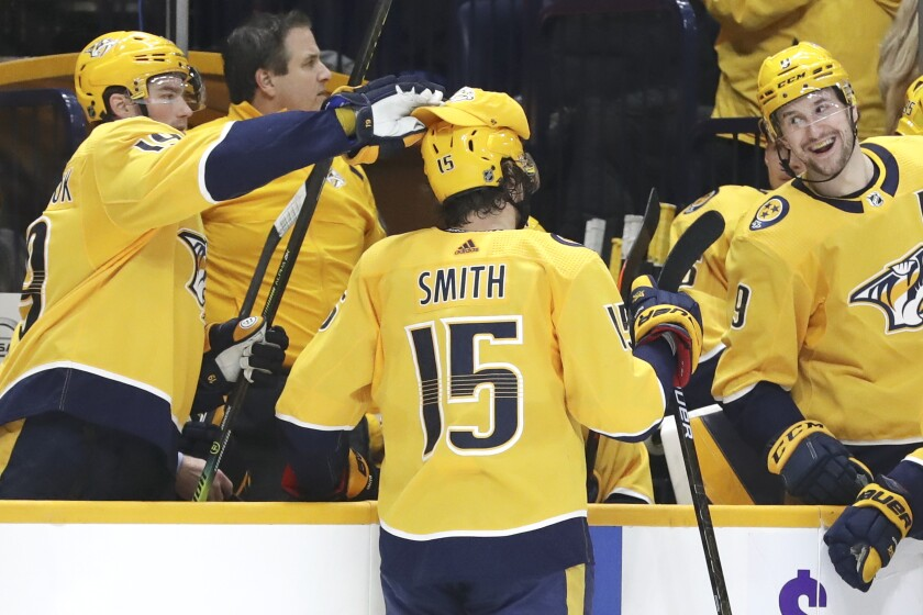 Nashville Predators' Calle Jarnkrok (19), left, of Sweden, puts a cap on right wing Craig Smith (15) after Smith scored his third goal for a hat trick against the New York Islanders in the second period of an NHL hockey game Thursday, Feb. 13, 2020, in Nashville, Tenn. Predators left wing Filip Forsberg (9), also of Sweden reacts. (AP Photo/Mark Humphrey)