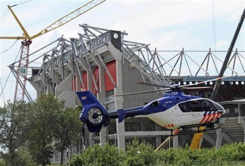 A helicopter flies near the collapsed stadium in Enschede, Netherlands, Thursday, July 7, 2011. A section of a Dutch football stadium collapsed during off-season construction work Thursday, trapping people underneath, police said. No match was being played at the FC Twente stadium at the time of the collapse and those trapped were believed to be workers. Local newspaper De Twentsche Courant, citing unnamed workers at the stadium, reported on its website that 12 people were injured in the accident. (AP Photo/Martin Meissner)